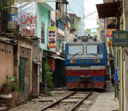 Diesel train coming down the train tracks through a narrow street in Hanoi showing how close the inhabitants live to the tracks. Image shot 2014. Exact date unknown.