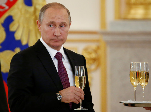 Russia's President Putin holds a glass during a ceremony of receiving diplomatic credentials from foreign ambassadors at the Kremlin in Moscow