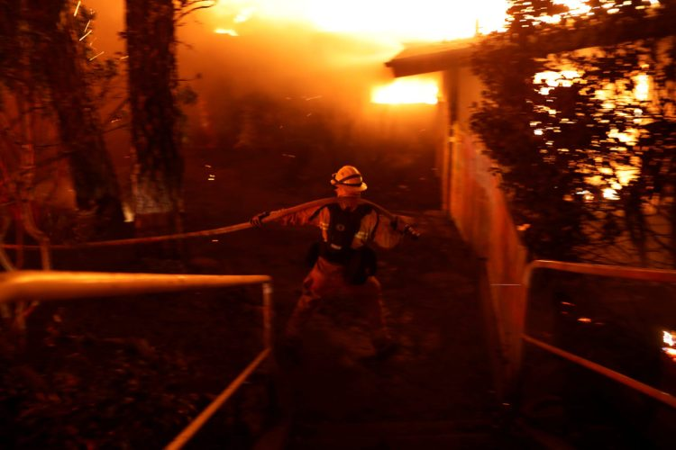 A firefighter drags a hose as he battles the Camp Fire in Paradise