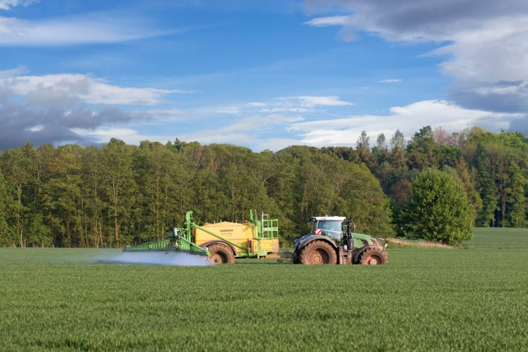 Farmer in tractor spraying herbicides over field with trailed sprayer in spring.