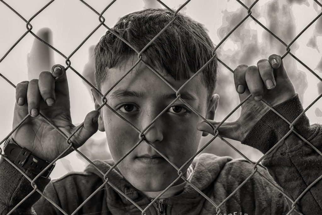 Immigrant boy behind wire cage