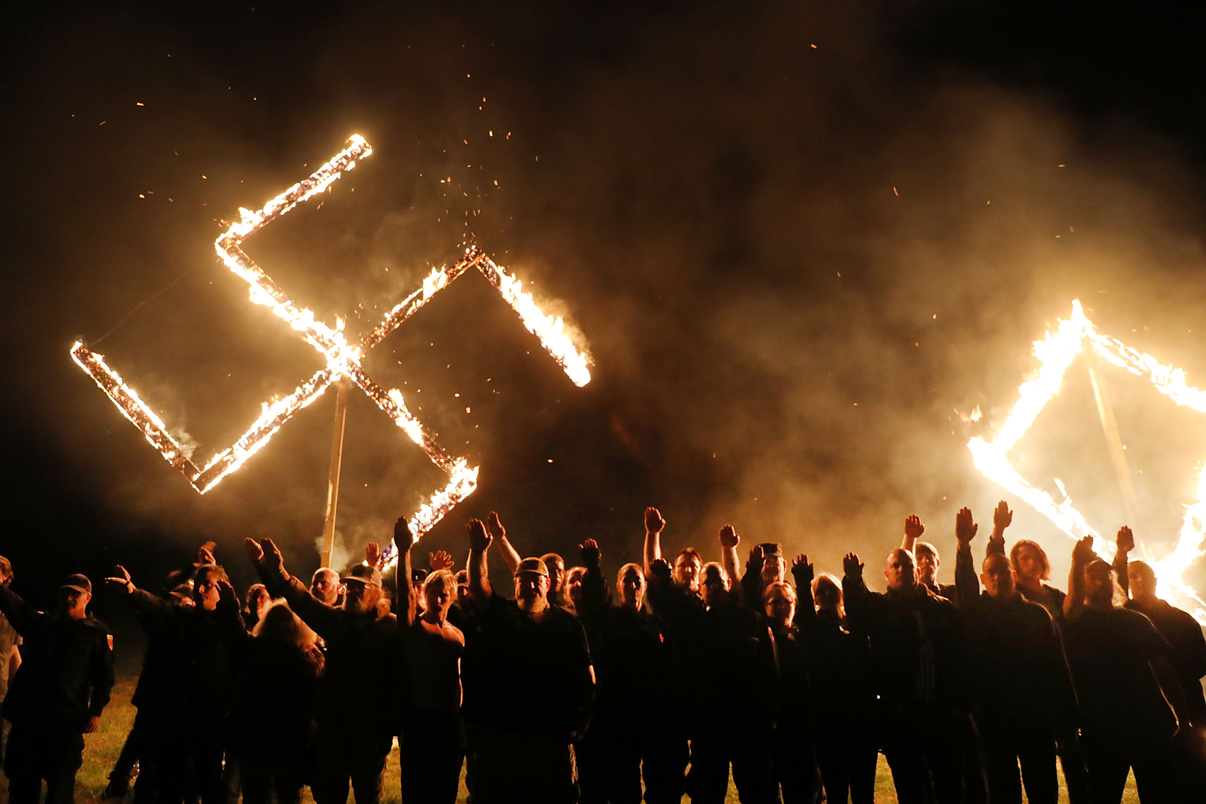 white supremacists giving Nazi salute with huge swastika burning